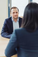 Geschäftsmann im Bewerbungsgespräch mit einer Bewerberin