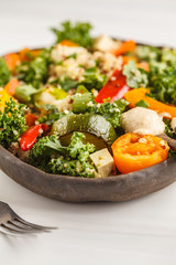 Healthy vegan salad with roasted vegetables, tahini, quinoa and kale. Clean eating concept.