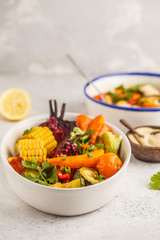 Salad with baked vegetables with tahini in white plate, white background. Clean eating concept.