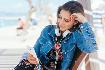 entspannte junge frau sitzt am meer und hört musik mit ihrem smartphone