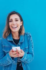 lachende frau mit mobiltelefon steht vor einer blauen wand