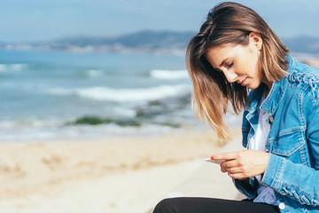 junge frau sitzt am meer und schaut nachdenklich auf ihr mobiltelefon