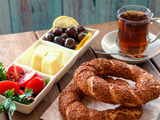 turkish bagel on wooden table, tea and breakfast plate. Tomatoes, cheese, olives