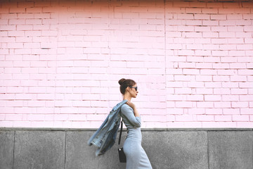 Street Style Shoot Woman on Pink Wall. Swag Girl Wearing Jeans Jacket, grey Dress, Sunglass. Fashion Lifestyle Outdoor Wall mural