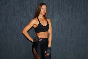 athletic sporty woman in fitness gloves on dark background in gym