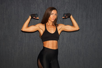 muscular sportswoman showing biceps on dark background in gym