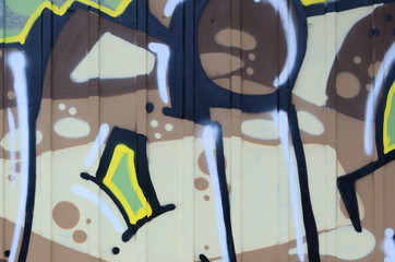 Fragment of graffiti drawings. The old wall decorated with paint stains in the style of street art culture. Colored background texture