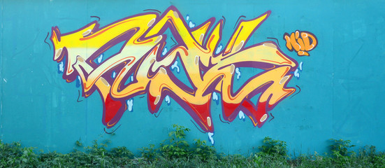 Full and acomplished graffiti artwork. The old wall decorated with paint stains in the style of...