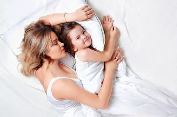 Smiling sleepless little girl with mom in bed