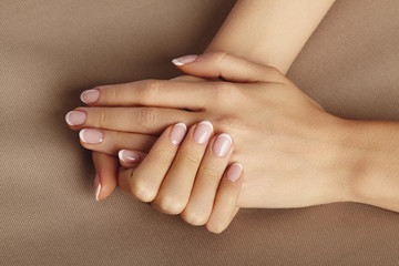 Foto op Canvas Manicure Young Female Palm. Beautiful Glamour Manicure. French Style. Nail polish. Care about Hands and Nails, clean Skin