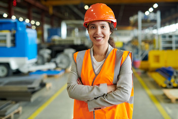 Waist up portrait of cheerful young woman wearing hardhat smiling happily looking at camera while posing confidently in production workshop, copy space