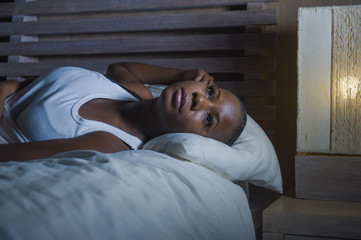 dramatic lifestyle portrait of young sad and depressed black afro American woman on bed sleepless suffering headache insomnia sleeping disorder