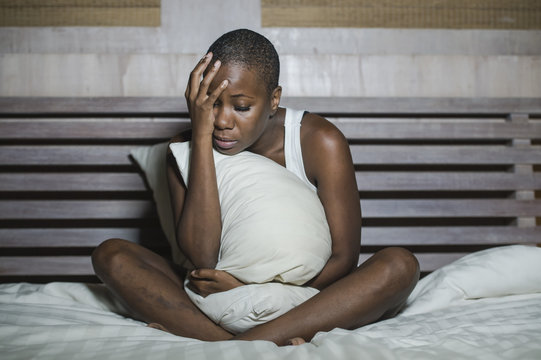 young sad depressed black afro American woman in bed sleepless feeling desperate worried suffering depression problem insomnia sleeping disorder
