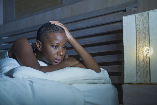 dramatic lifestyle portrait of young sad and depressed black african American woman on bed sleepless suffering headache insomnia sleeping disorder