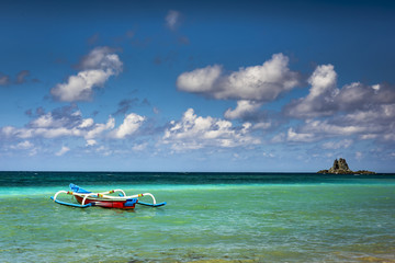 Scenery of beautiful seascape Lombok beach with wooden fishing boat, small island and white cloud blue sky background