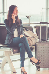 Airport woman on smart phone at gate waiting in terminal. Air travel concept.
