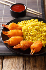 Chinese fast food crab claws in breadcrumbs surimi with spicy yellow rice close-up on a plate. vertical