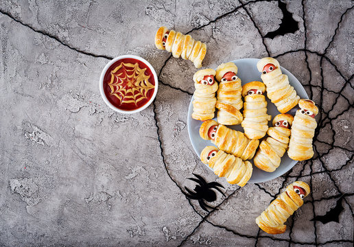 Scary sausage mummies in dough with funny eyes on table.  Halloween food. Top view. Flat lay. Banner