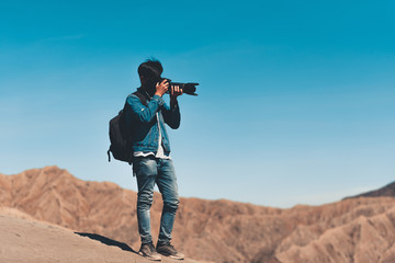 Portrait of photographer is shooting picture on top of mountain at sunrise scene