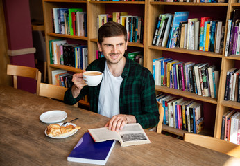 Warsaw/ Poland - August 15, 2018: Handsome brunet man reading book in library and drinking coffee with fresh cake. Student having dinner, sitting at table. Stylish loft interior of university cafe.