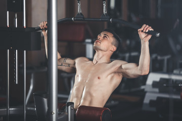 Tattooed topless man is exercising chest muscles with equipment. He is sitting and using vertical row while pulling down its handle. Male is training with weight for better achievement