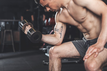 Shredded topless sportsman is concentrated on upper body training. He is doing one arm curls with dumbbell while sitting on bench and bending body