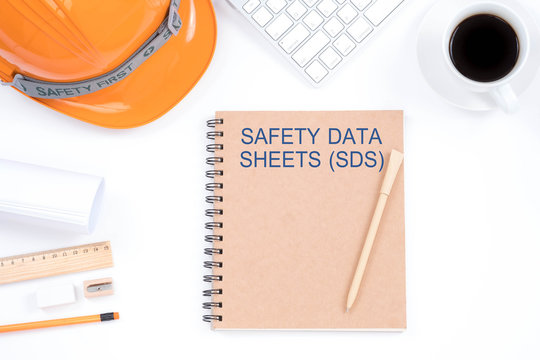 Concept SAFETY DATA SHEETS (SDS). Top viwe of modern workplace with safety helmet, office supplies, a cup of coffee and keyboard on white background. Safety & Health.