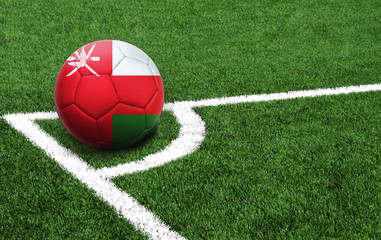 soccer ball on a green field, flag of Oman