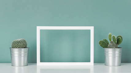 Collection of various cactus plants in metal pots. Potted cactus plants on white shelf against turquoise colored wall and picture frame mock up.