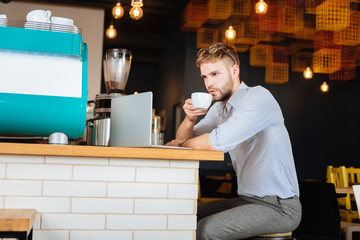 Blonde-haired businessman. Blonde-haired businessman wearing stylish trousers and shirt having some coffee while working