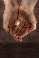 Dirty child's hands with one euro coin, poverty symbol, with copy space