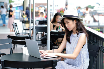 Young asian woman using laptop computer sitting at cafe outdoors, people and technology, lifestyles, education, working outdoors, business concept