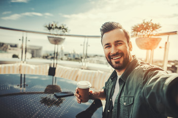 Nice shot. Cheerful male customer holding cup with hot beverage while taking photo. He is sitting at the table in outdoor cafe