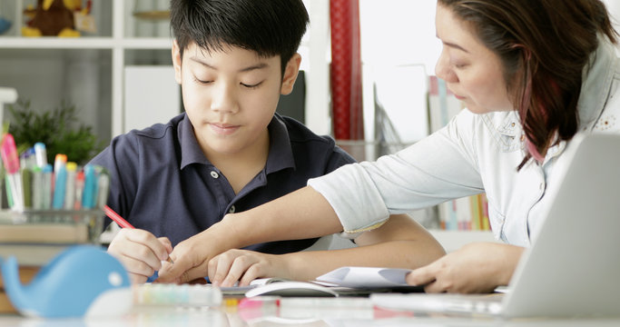 Cute asian mother helping your son doing your homework .