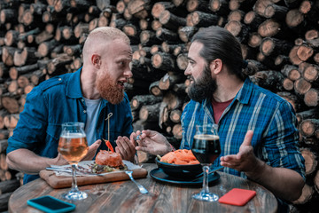Bearded men. Two bearded man feeling good while speaking about something drinking tasty craft beer
