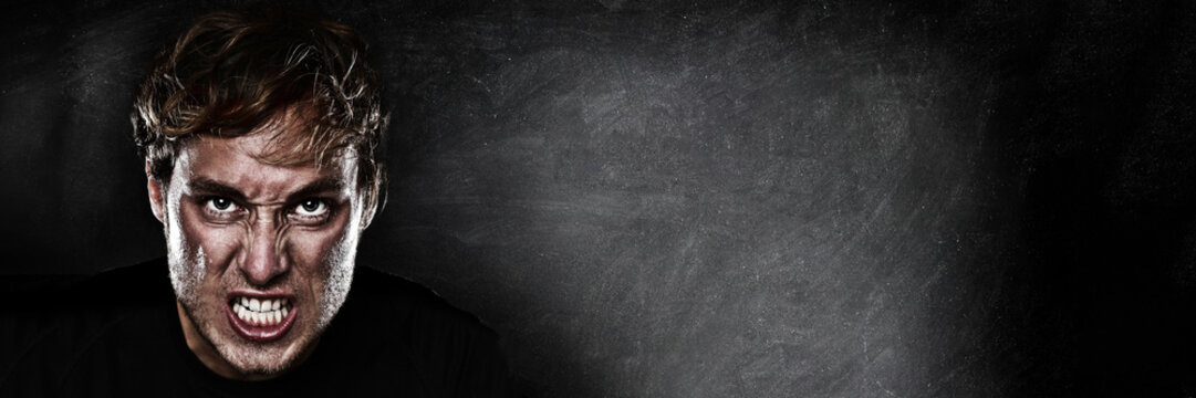 Angry agressive man face ready to fight on blackboard chalk board black texture background panoramic banner for advertising. Scary upset athlete focused to win.