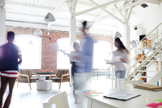 Blurred motion of young business colleagues working in a busy open plan office