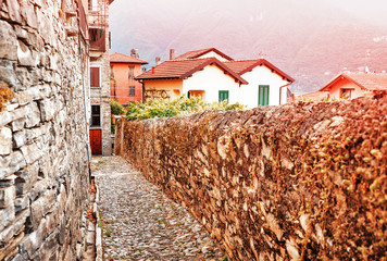 Wall Mural - Alpine Village Carate Urio on Como lake. Spectacular sunrise city scene on narrow street in old medieval town. Typical old Italian town scenery. Vintage style photo.