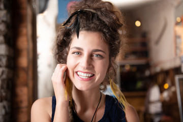 Woman laughing. Beautiful woman wearing nice yellow earrings laughing while listening to jokes of friends
