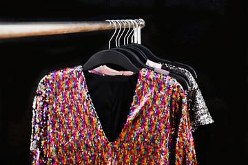 sequins colorful sundress hanging on hanger– black background,