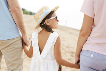Little girl in sunglasses and hat holding her parents by hands during chill on the beach
