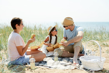Cute little girl sitting next to her father and talking to him at family picnic while having sandwiches and drinks