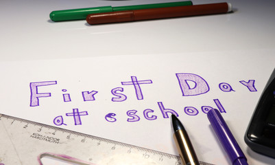 First day at school is writing on paper. You can see part of calculation, pen, felt-tip pen, rule.
