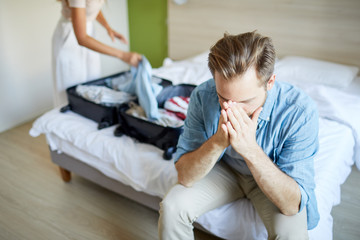 Young man sitting on bed and praying while his wife getting suitcase before leaving
