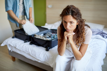 Stressed young woman sitting on bed while her husband preparing suitcase with things before leaving