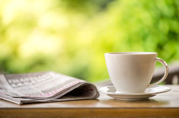 good morning coffee cup with news paper on nature green background in garden