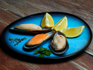 Fresh mussels and quartered lemons set on a blue plate, placed on a dark brown wooden surface