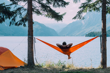 Back view of man silhouette relaxing on orange hammock between two trees pine enjoying the view at...