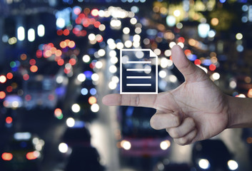 Document flat icon on finger over blurred colorful night light city with cars and road, Business technology internet communication concept