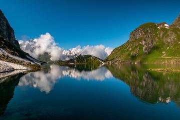 Swiss alps water reflection in Lac de Louvie - mountain lake above Val de Bagnes valley, Switzerland.